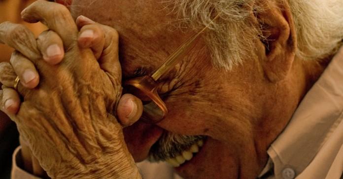 Manoel de barros com mão no rosto, olhos fechados e sorrindo