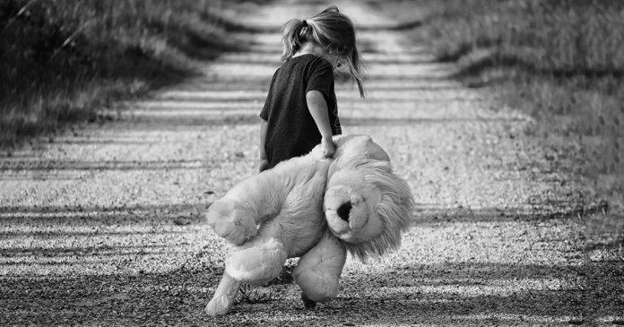 Foto de uma criança triste por problemas no círculo familiar, de costas carregando um urso de pulucia