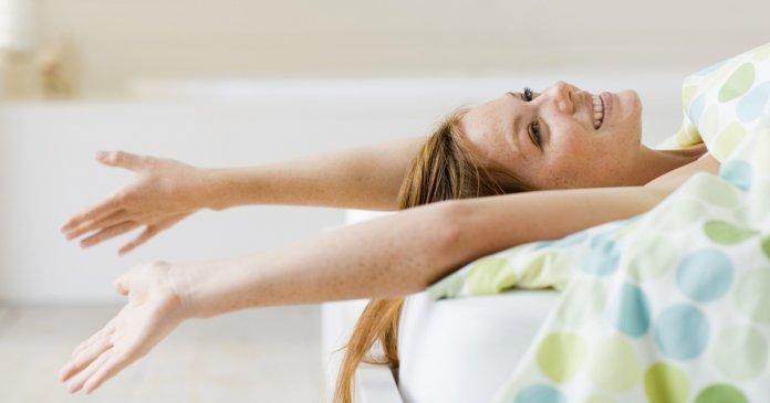 foto de mulher deitada na cama feliz sozinha