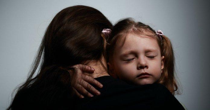 mulher abraçando criança assustada